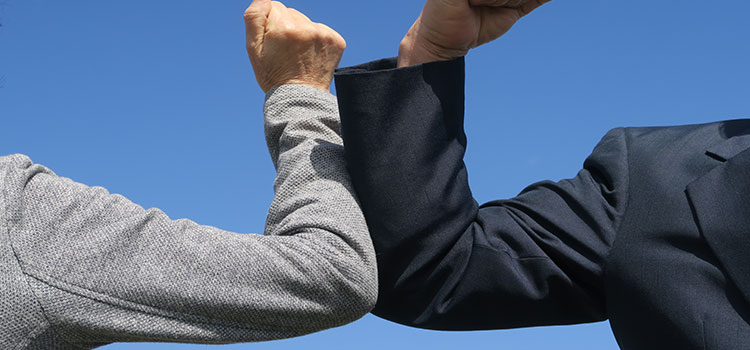 Two business professionals elbow bumping - Vendor's Standard Terms and Conditions